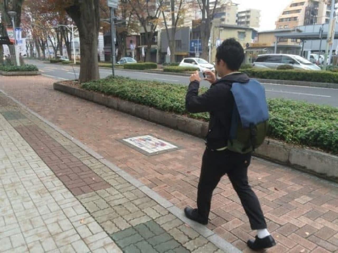スマートフォンで路面を撮影する男性