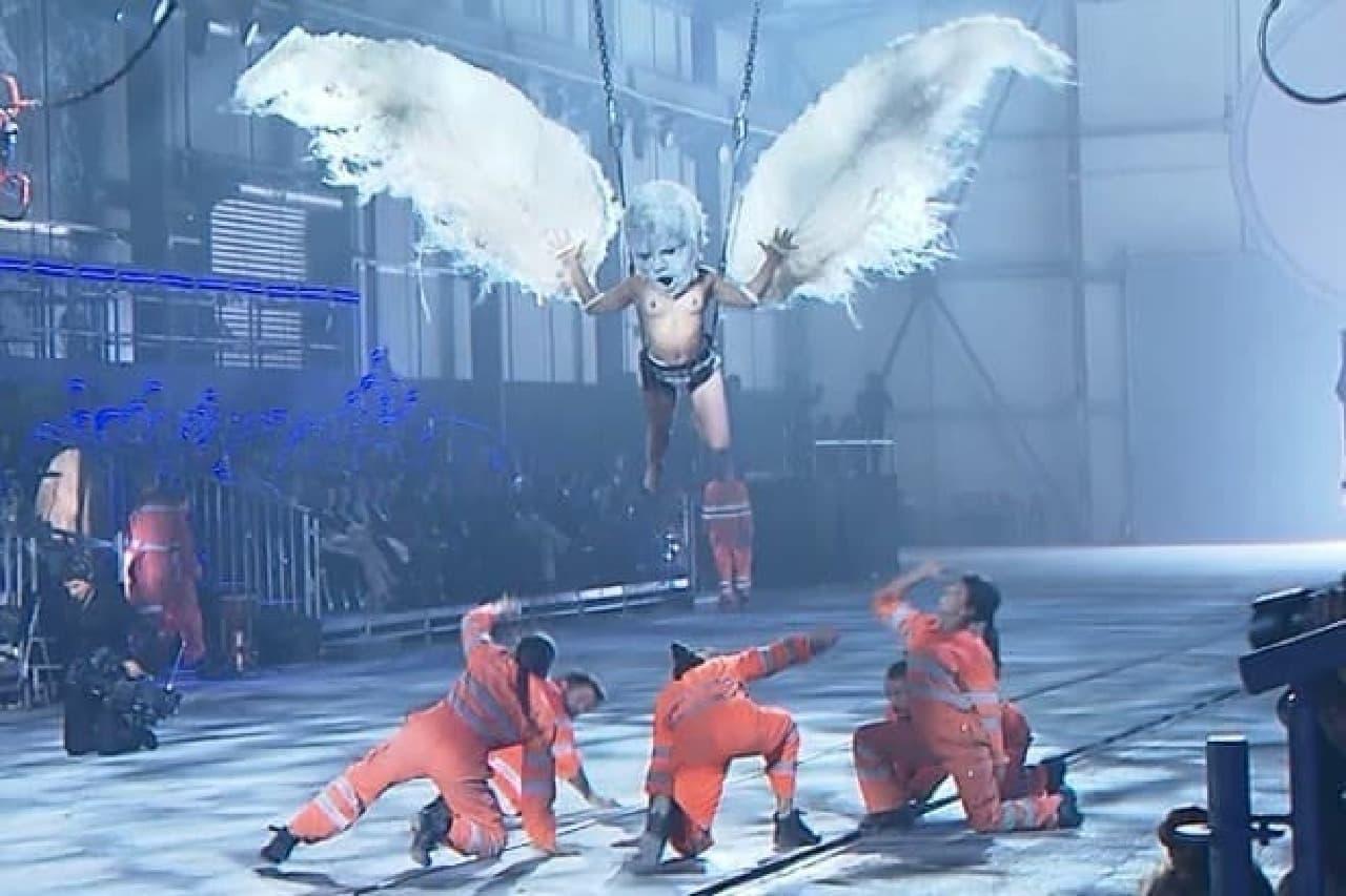 白い翼をつけて舞う半裸の人物
