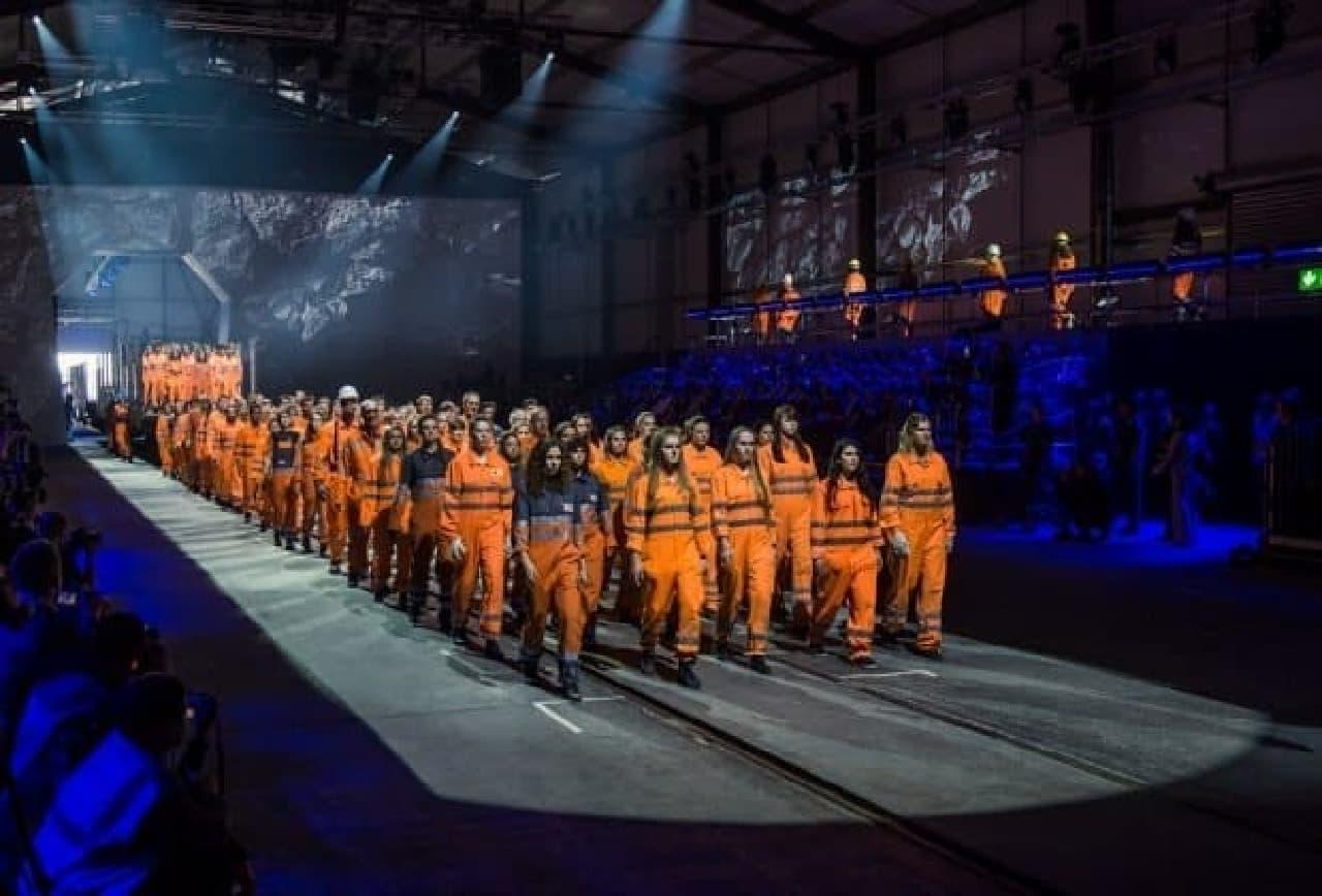 トンネル開通イベントで行進する作業服を着たアーティスト達