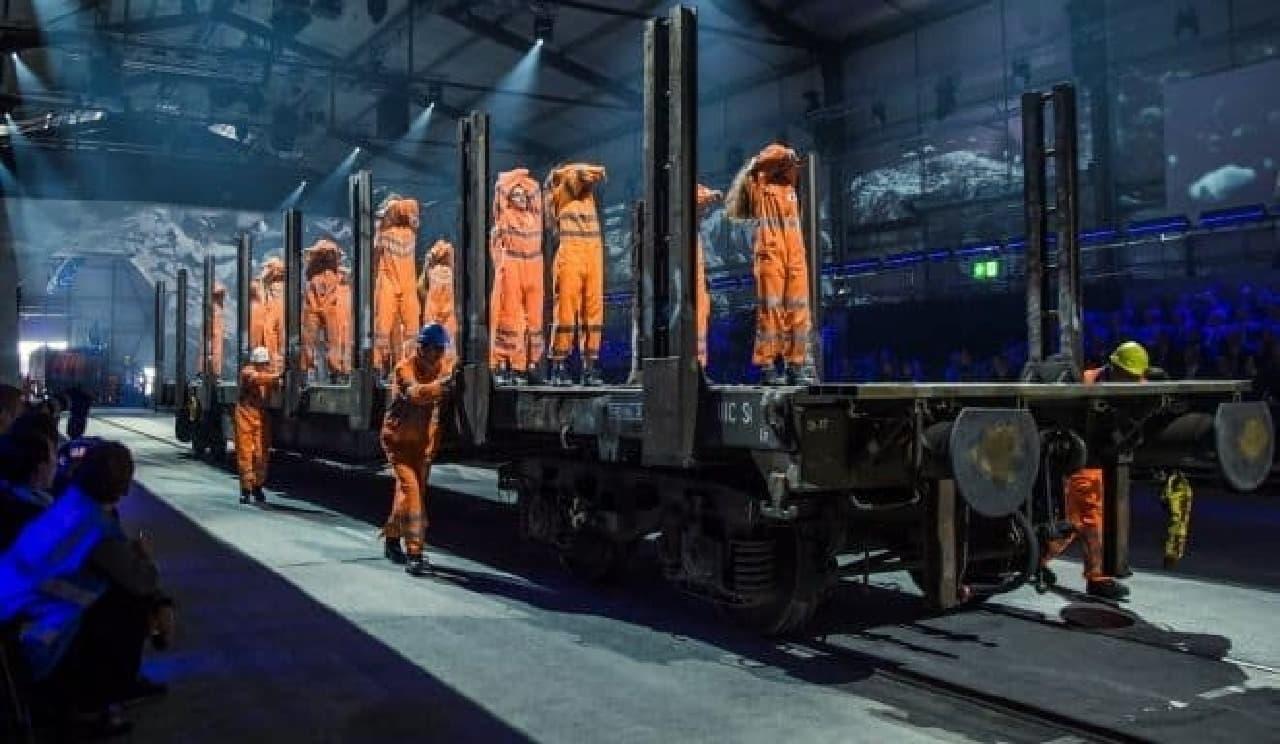 トンネル開通式典で台車に載って移動する作業服を着たアーティスト達