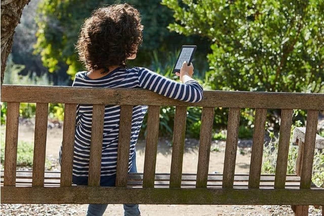電子書籍リーダー「Kindle」を持ってベンチに腰掛ける女性