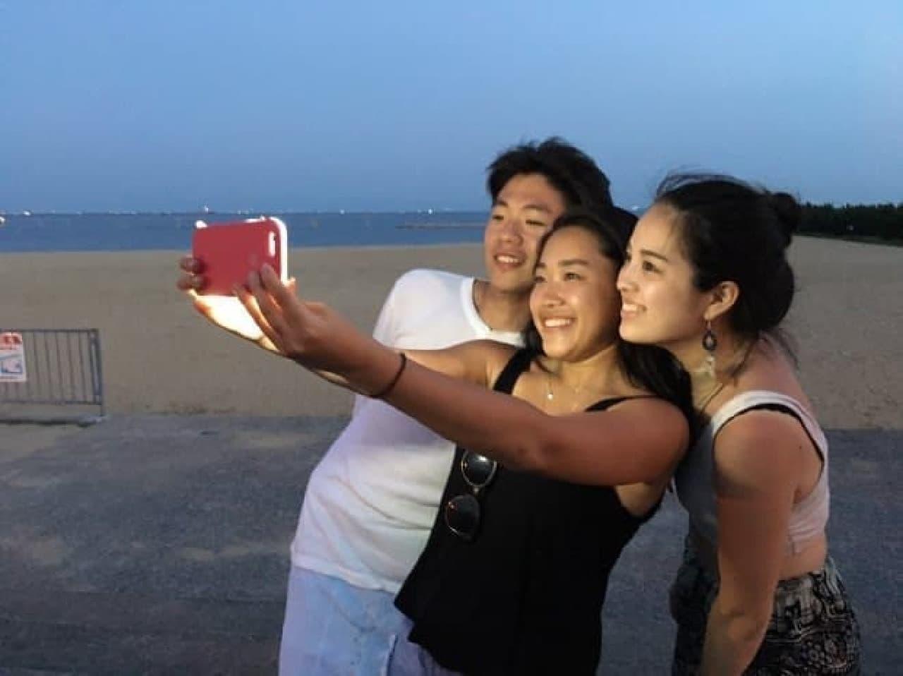 セルフィー用iPhoneケースを使う男女3人