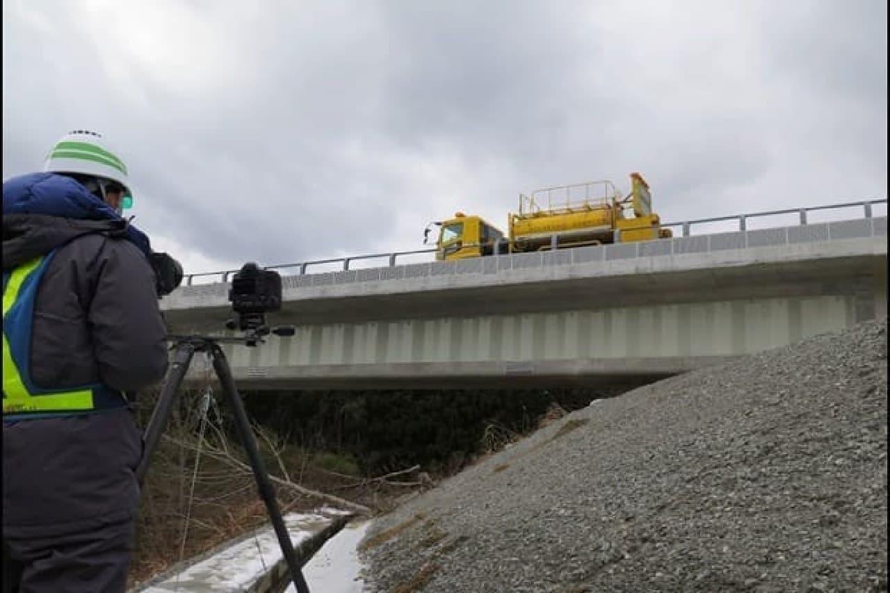 橋梁のたわみを撮影する技術者