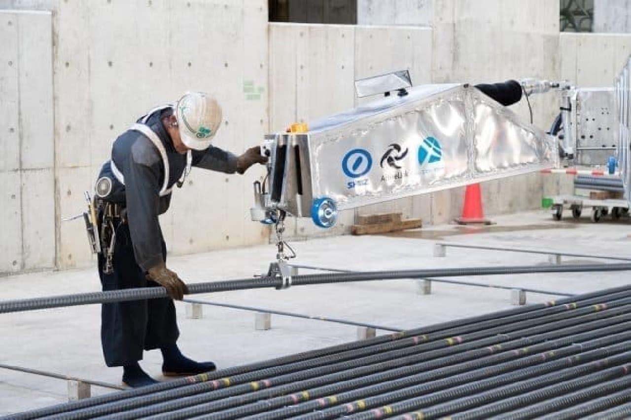 ロボットを導く作業員