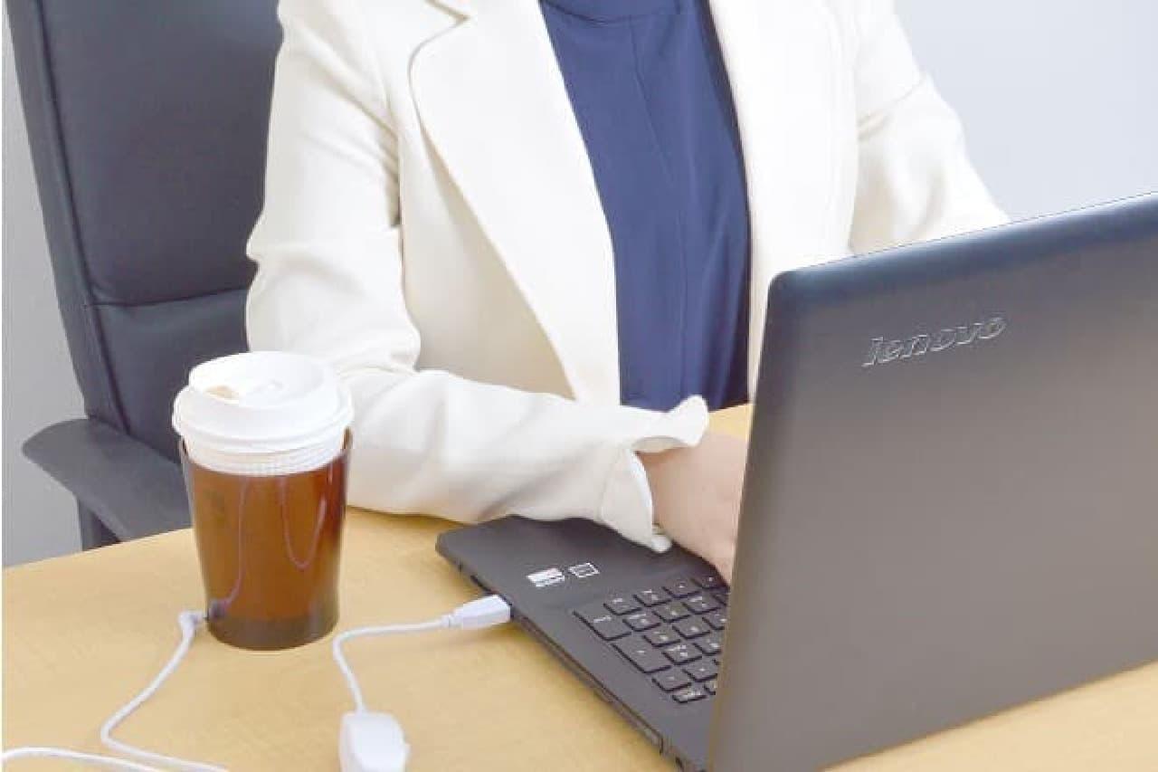 コーヒーを横に置いてPC操作する女性