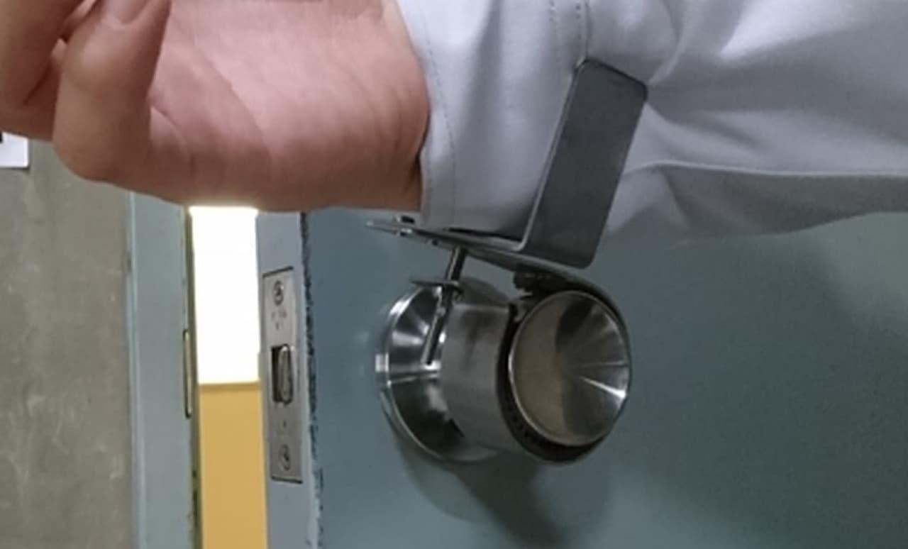 手を洗った後でドアノブを握りたくない! ― 丸いドアノブを腕や肘で開閉可能にする「ノブフック#1」